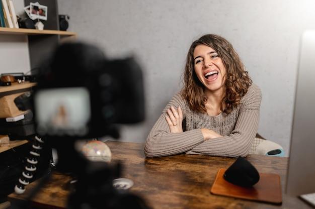 Glimlachende jonge vrouwenzitting bij een bureau dat met de camera spreekt. vlog-concept.