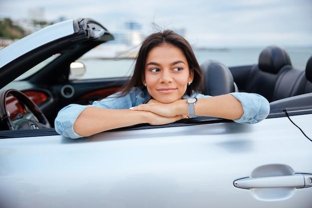Glimlachende jonge vrouwenzitting in haar converteerbare auto op strand