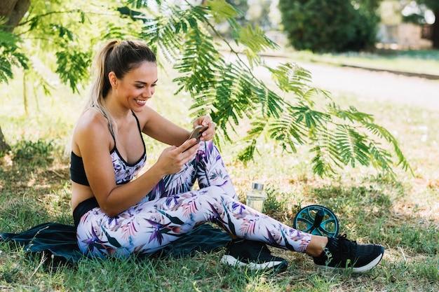 Glimlachende jonge vrouwenzitting onder de boom die mobiele telefoon bekijken