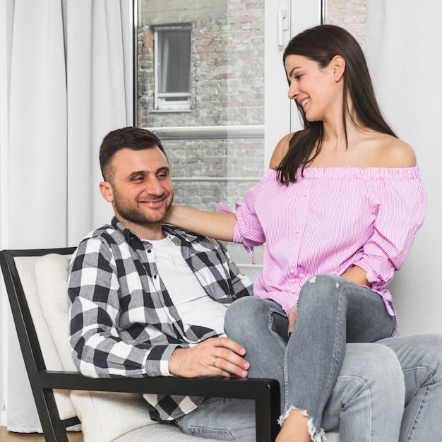 Glimlachende jonge vrouwenzitting op de overlappingszitting van haar vriend op stoel