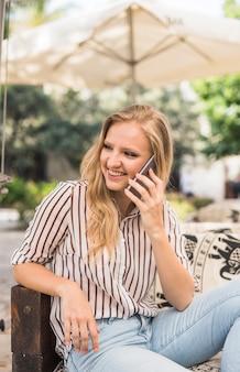 Glimlachende jonge vrouwenzitting op openluchtlaag die mobiele telefoon met behulp van