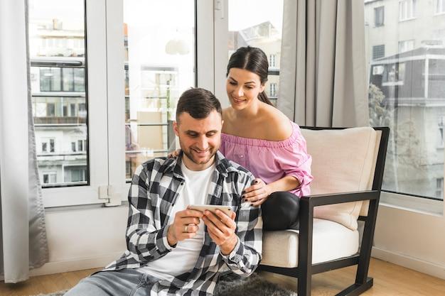 Glimlachende jonge vrouwenzitting op stoel die haar vriend bekijkt die mobiele telefoon met behulp van