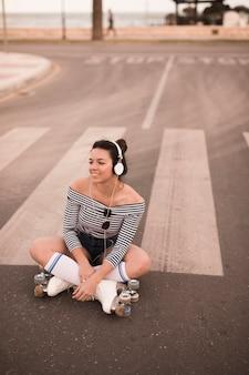 Glimlachende jonge vrouwenzitting op weg die rolschaats het luisteren muziek op hoofdtelefoon dragen