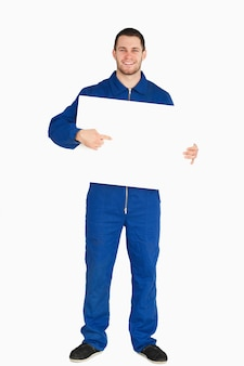 Glimlachende jonge werktuigkundige die in ketelpak op banner in zijn handen richt