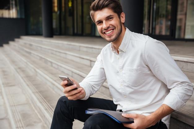 Glimlachende jonge zakenman die buiten zit en mobiele telefoon gebruikt