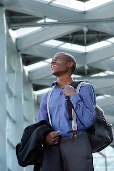 Glimlachende jonge zakenman die door station met zak loopt