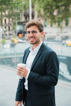 Glimlachende jonge zakenman die meeneemkoffiekop ter beschikking houden