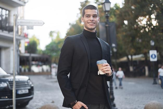 Glimlachende jonge zakenman die naar het werk met koffie gaat