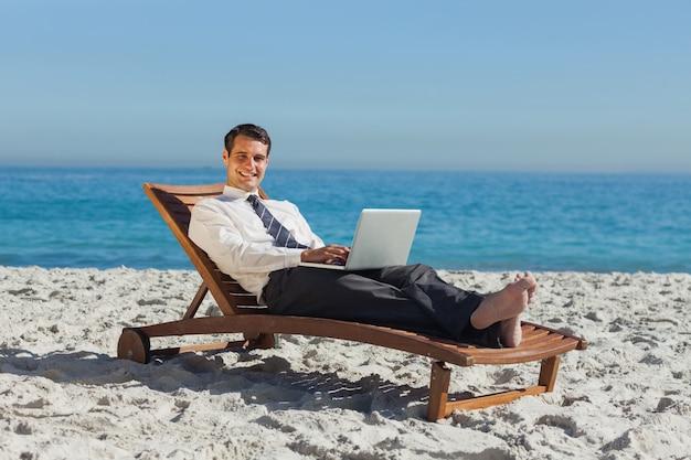 Glimlachende jonge zakenman die op een ligstoel met zijn laptop ligt