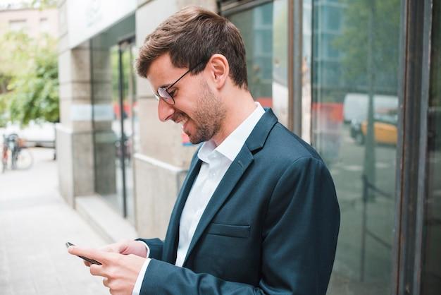 Glimlachende jonge zakenman die smartphone gebruikt