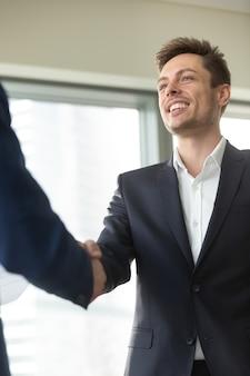 Glimlachende jonge zakenman die zwart kostuum draagt die mannelijke hand schudt,
