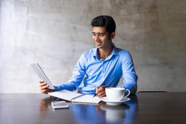 Glimlachende jonge zakenman het drinken koffie bij koffie, die videovraag hebben en nota's schrijven.
