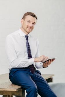 Glimlachende jonge zakenman in elegante kleren gelukkig om inkomensbericht op moderne tabletcomputer te ontvangen