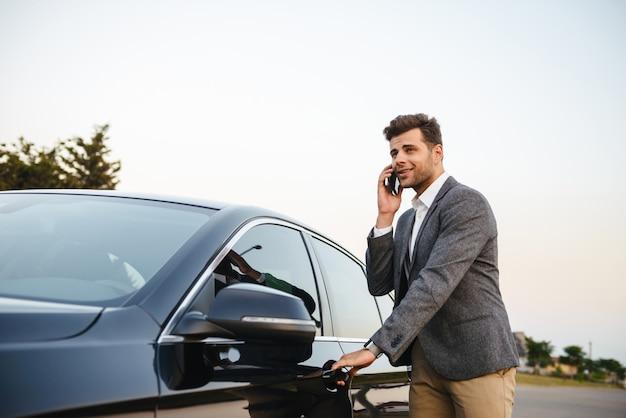 Glimlachende jonge zakenman in kostuum dat zich bij zijn auto bevindt