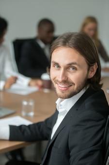 Glimlachende jonge zakenman in kostuum die camera op vergadering bekijken