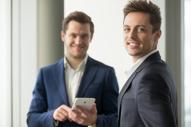 Glimlachende jonge zakenman kijken camera, applicatie ontwikkelen