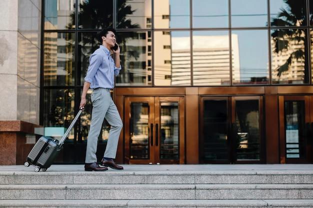 Glimlachende jonge zakenman met behulp van mobiele telefoon tijdens het wandelen met koffer in de stad. levensstijl van moderne mensen. volledige lengte