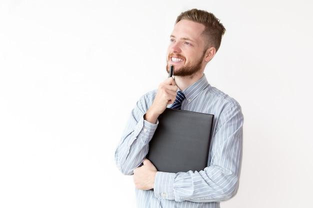 Glimlachende jonge zakenman met peinzende uitdrukking