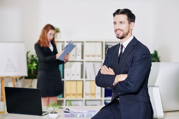 Glimlachende jonge zakenman zittend op tafel met armen gevouwen en wegkijken