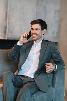 Glimlachende jonge zakenmanzitting op bank die door mobiele telefoon spreekt