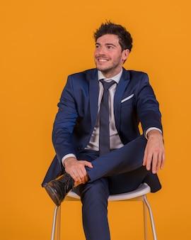 Glimlachende jonge zakenmanzitting op stoel die weg tegen een oranje achtergrond kijken