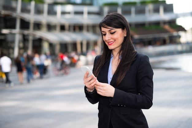 Glimlachende jonge zakenvrouw die haar mobiele telefoon gebruikt