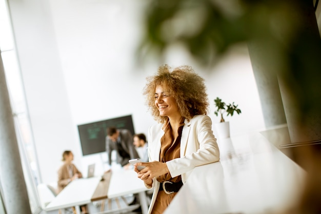 Glimlachende jonge zakenvrouw met behulp van mobiele telefoon in moderne kantoren