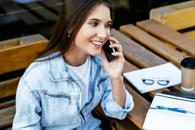 Glimlachende jonge zakenvrouw zittend op terras op straat, praten over smartphone. duizendjarige vrouw werkt