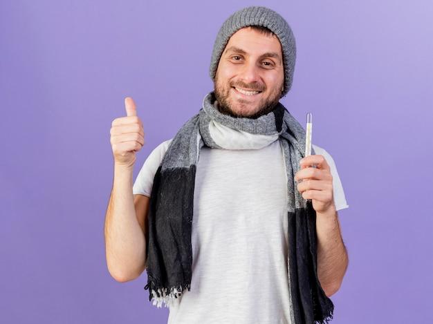 Glimlachende jonge zieke man die de winterhoed met de thermometer van de sjaalholding draagt die duim toont die omhoog op paars wordt geïsoleerd