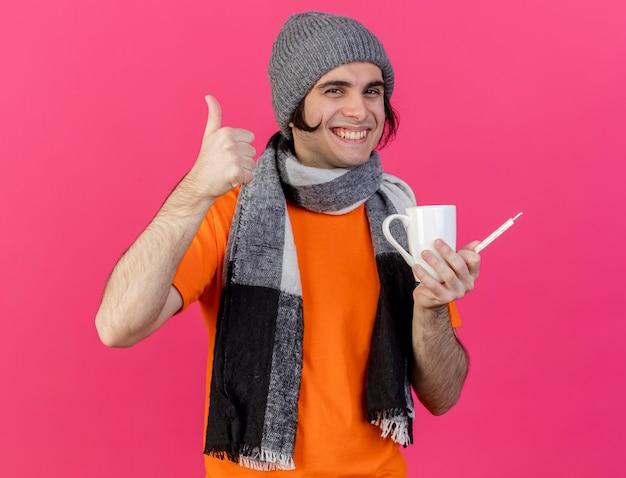 Glimlachende jonge zieke man die de wintermuts met sjaal draagt die kopje thee met thermometer houdt die duim toont die omhoog op roze achtergrond wordt geïsoleerd