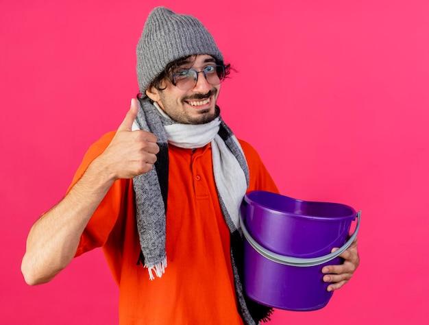 Glimlachende jonge zieke man met bril, muts en sjaal met plastic emmer kijkend naar de voorkant met duim omhoog geïsoleerd op roze muur
