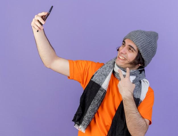 Glimlachende jonge zieke man met muts met sjaal neemt een selfie met vredesgebaar geïsoleerd op paarse achtergrond