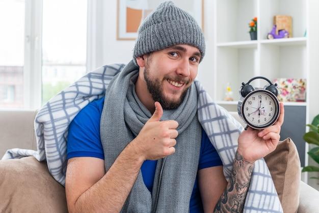 Glimlachende jonge zieke man met sjaal en wintermuts zittend op de bank in de woonkamer gewikkeld in deken met wekker met duim omhoog