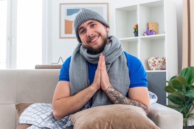 Glimlachende jonge zieke man met sjaal en wintermuts zittend op de bank in de woonkamer met kussen op zijn benen kijkend naar de camera die handen in gebedsgebaar houdt
