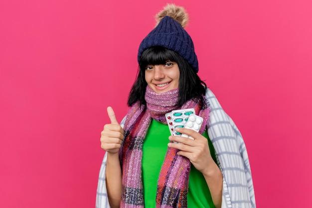 Glimlachende jonge zieke vrouw die de wintermuts en sjaal draagt die in plaid wordt verpakt die medische pillen houdt die voorzijde toont met duim omhoog geïsoleerd op roze muur met exemplaarruimte