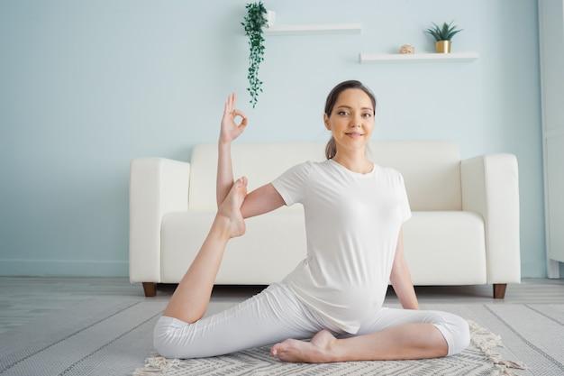 Glimlachende jonge zwangere brunette vrouw beoefent thuis yoga op de vloer en kijkt naar camera copyspace