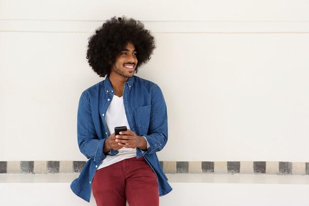 Glimlachende jonge zwarte mens die cellphone gebruikt