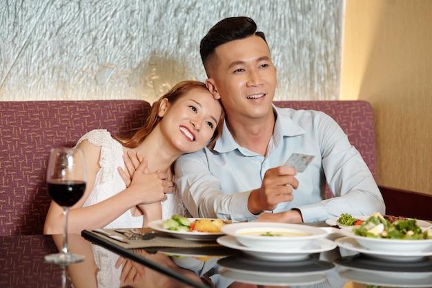 Glimlachende jongeman die met creditcard betaalt voor het avondeten voor hem en zijn vriendin