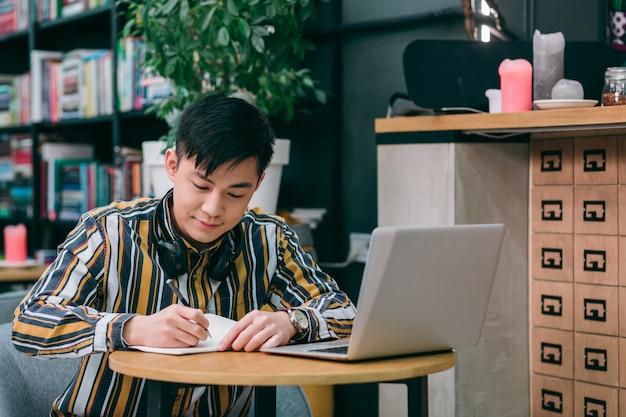 Glimlachende jongeman die met een laptop aan tafel zit en blij kijkt terwijl hij in een notitieboekje schrijft