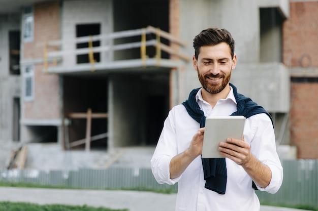 Glimlachende jongeman in wit overhemd die naar het tabletscherm kijkt terwijl hij tussen hoge gebouwen staat. bebaarde ingenieur geniet van favoriete baan in de frisse lucht.