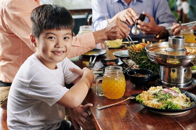 Glimlachende jongen bij diner met familieleden