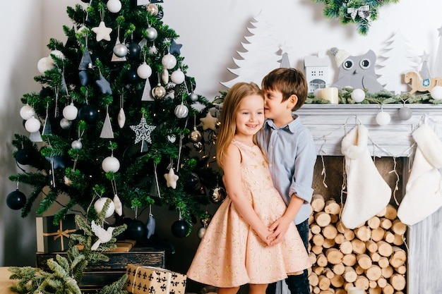 Glimlachende jongen die aan oor van zijn leuk en mooi meisje in fron van cristmasboom met open haard fluisteren.