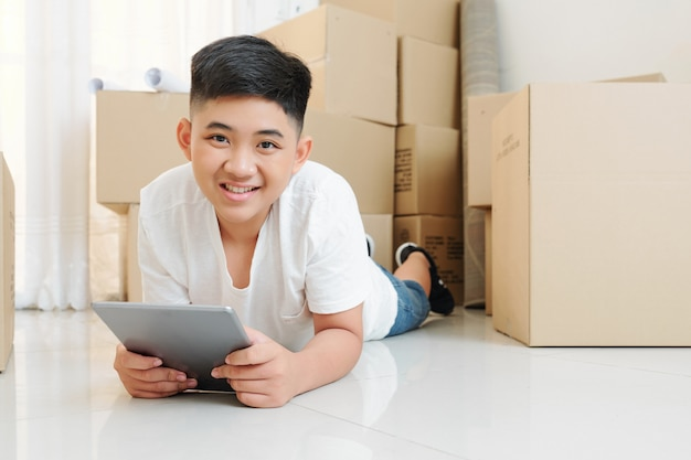 Glimlachende jongen die app op tablet gebruikt