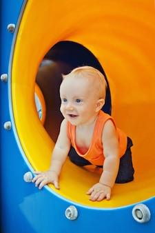 Glimlachende jongen die door de speelplaatsbuis kruipt