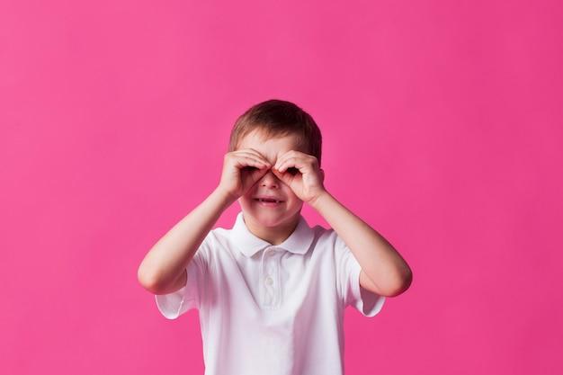Glimlachende jongen die door vingers als verrekijker over roze achtergrond kijkt