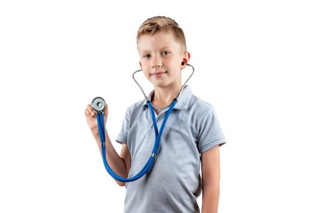 Glimlachende jongen die een stethoscoop in zijn handen houdt die op een witte achtergrond worden geïsoleerd