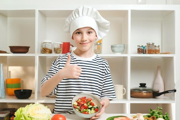 Glimlachende jongen die gezond voedsel kookt en duim toont. schattige kleine jongen met chef-kok hoed en uniform. koken voedsel concept. zoon die verse salade voorbereidt voor familiediner.
