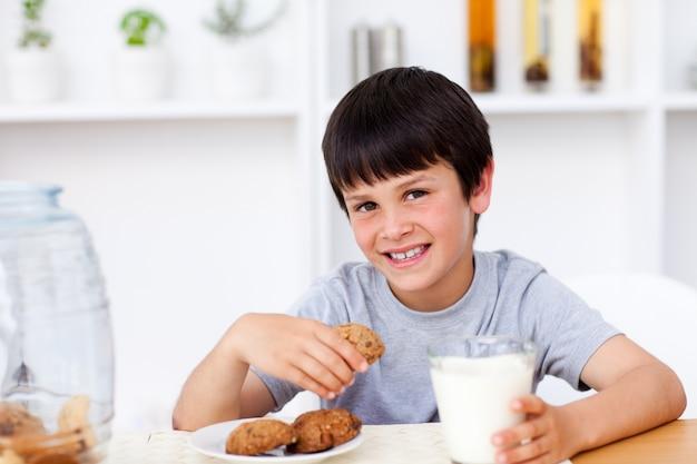 Glimlachende jongen die koekjes eet