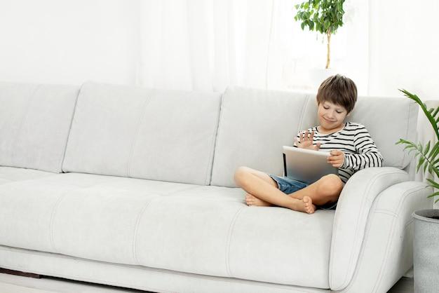 Glimlachende jongen die online babbelt en bij het computerscherm golft. kinderen en gadgets.