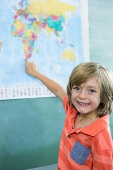 Glimlachende jongen die op kaart in klaslokaal richt